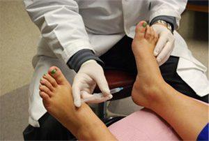 врач делает пациенту укол в пятку